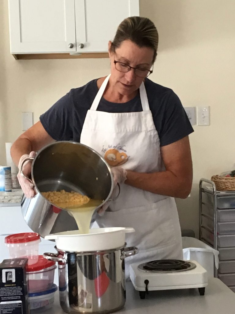 Kate draining the whey into the pot to keep the next step warm