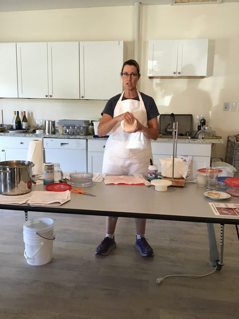 Kate showing us how to wrap the bandage around the pressed cheddar wheel