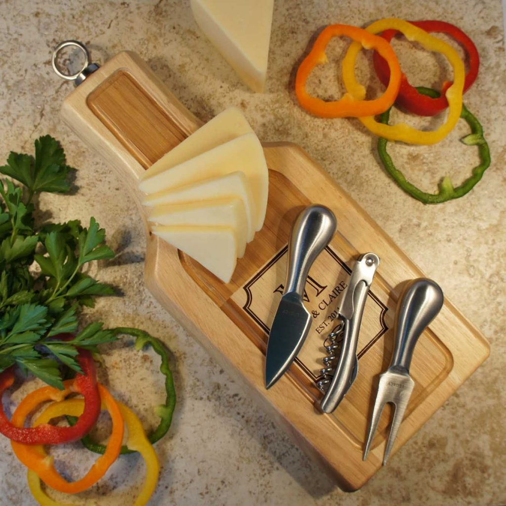 wine and cheese board with 2 knives and corkscrew